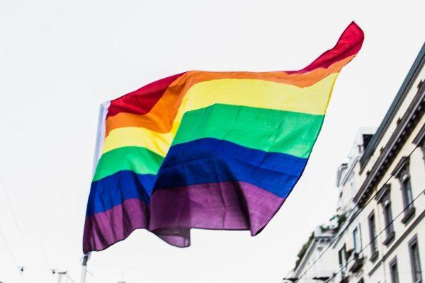 A rainbow flag flies over a city.