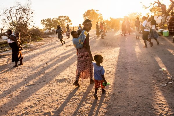 A woman walks among a crowd, holding the hand of a toddler and carrying a baby.
